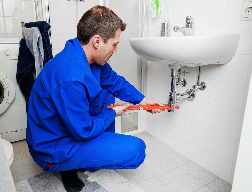 warmen plumber in a blue jumpsuit fixing a sink with a red wrench