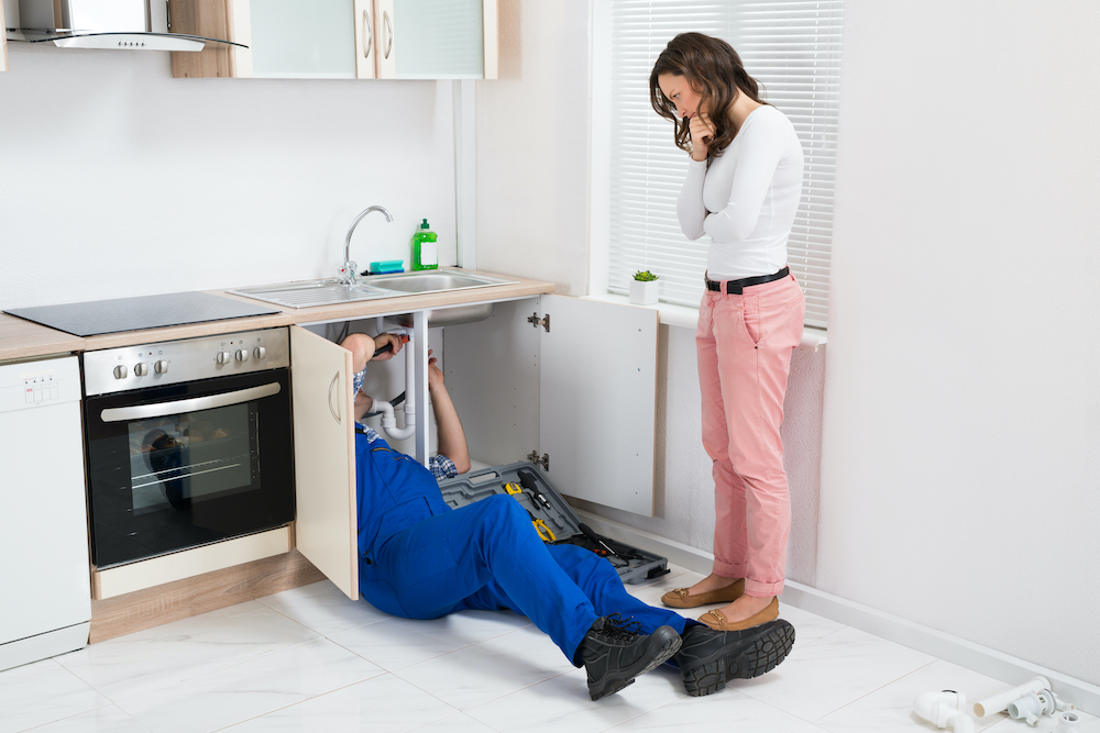 Young Repairman Repairing Sink Pipe While Woman Standing In The Kitchen