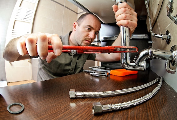 residential plumber fixing under a sink with red wrench