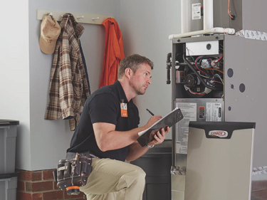 Plumber fixing gas furnace using electric and plumbing tools. Plumber in uniform working on gas furnace. Electric and plumbing tools, electric wire.